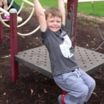 young boy swinging on bar