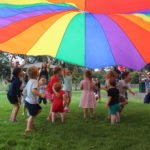 kids under rainbow parachute on grass