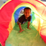 boy in rainbow colored tunnel