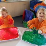 two girls with hands in green and red paint
