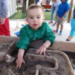 toddler with hands in mud
